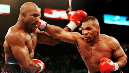 LAV14:SPORT-BOXING:LAS VEGAS,NEVADA,09NOV96 - Challenger Evander Holyfield (L)takes aright fist to the face from Mike Tyson during the first round of their WBA Heavyweight Championship fight at the MGM Grand hotel in Las Vegas, November 9. Holyfield defeated Tyson by TKO in the 11th round when the referee stopped the fight.      bps/Photo by Gary Hershorn REUTERS ORG XMIT: LAV14